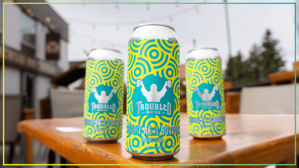 three cans of troubled monk bright as a button english bitter sitting on a wood patio table outside of the taproom.