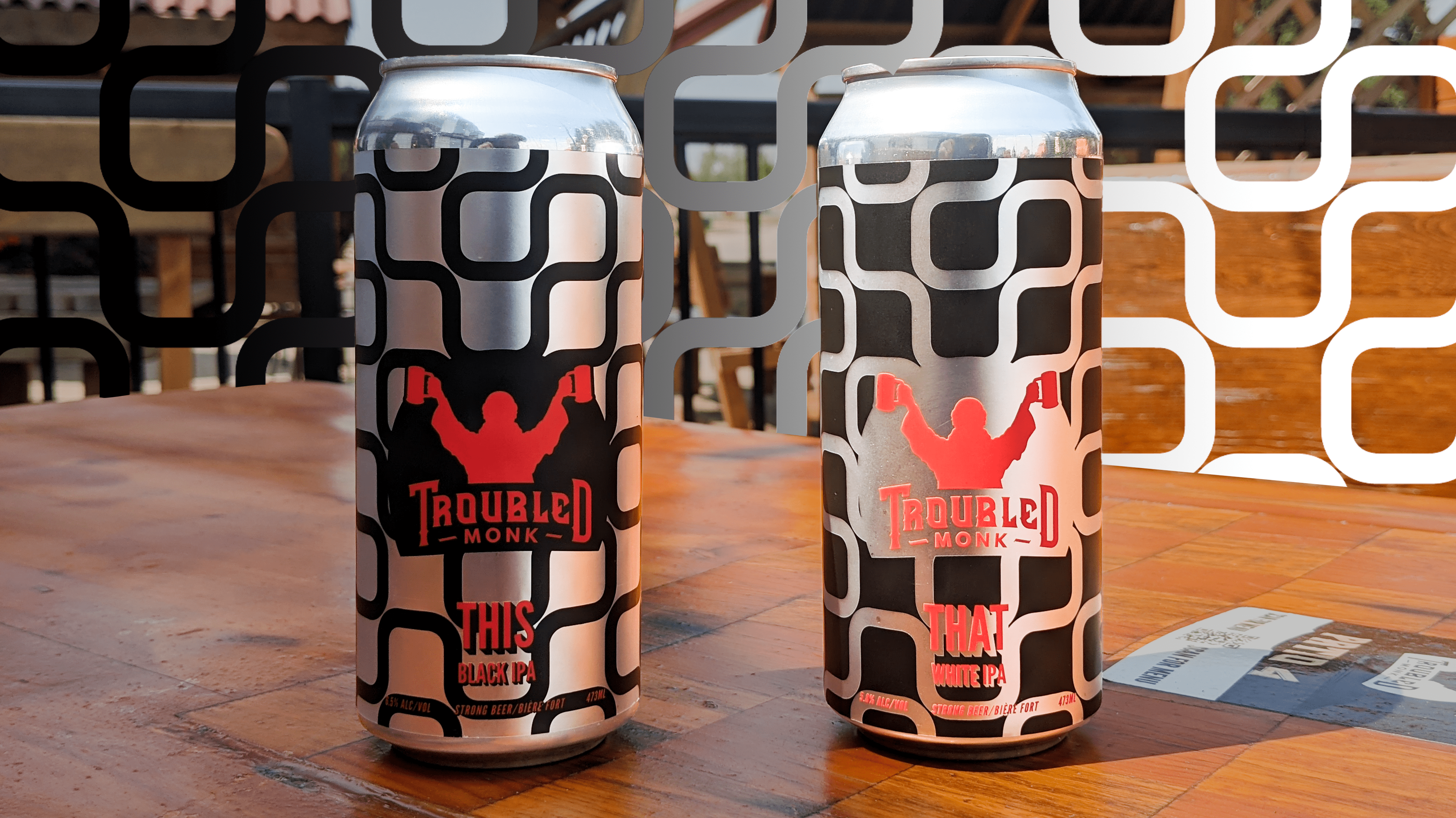 A can of THIS White IPA in silver and black, and a cna of THAT Black IPA in black and silver sitting on a table at troubled monk taproom