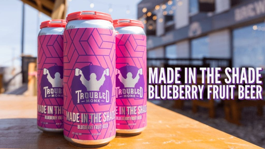 A four pack of tall cans of made in the shade blueberry fruit ale sitting on a table at troubled monk's patio.