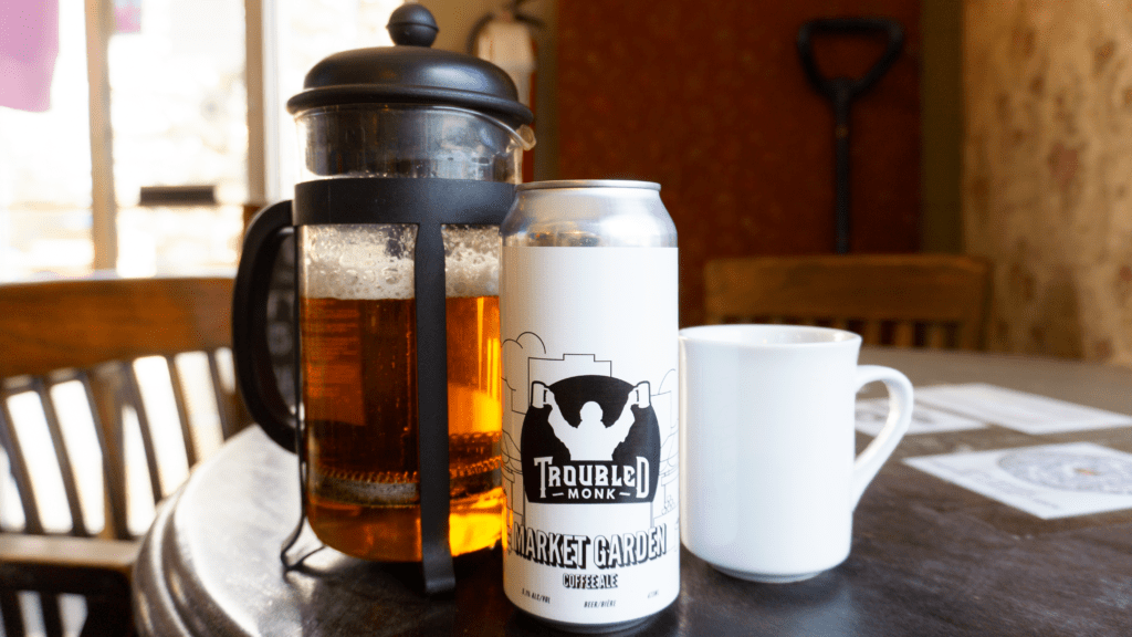 Picture of a coffee cup, a french press and a can of troubled monk's market garden coffee ale