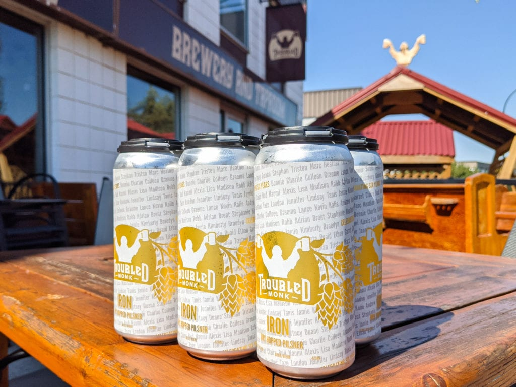 a six pack of tall iron dry hopped pislner cans sitting on a patio table at troubled monk's taproom