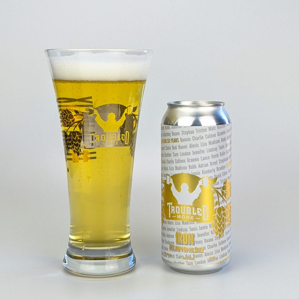 a picture of a pint of the golden coloured iron dry hopped pilsner in the commemorative free 20 oz pilsner glass and a can of iron dry hopped pilsner