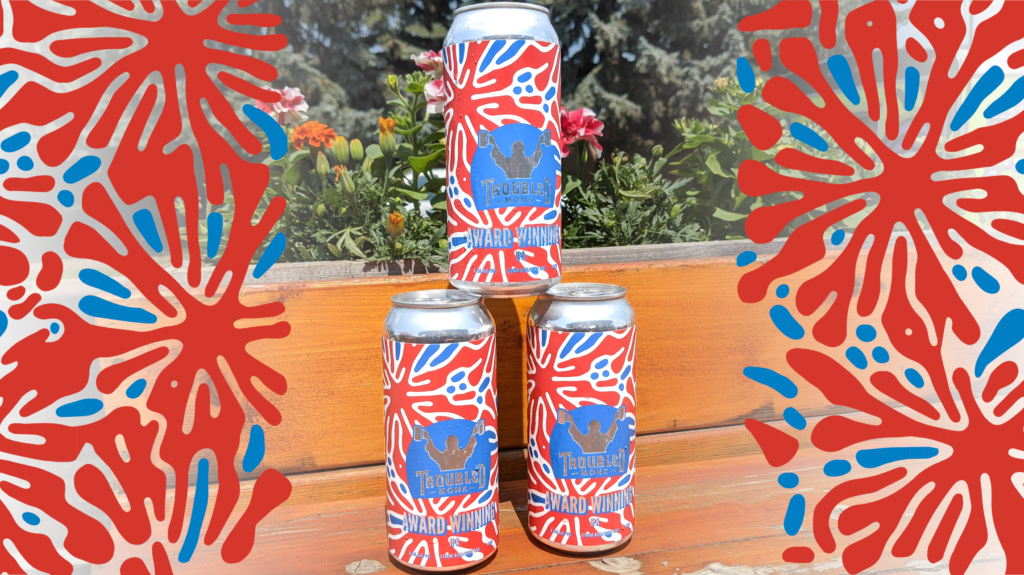 A picture of three cans of troubled monk award winning hazy ipa sitting on the patio with flowers behind. The can is blue and red, and blue and red graphics frame the three can stack.