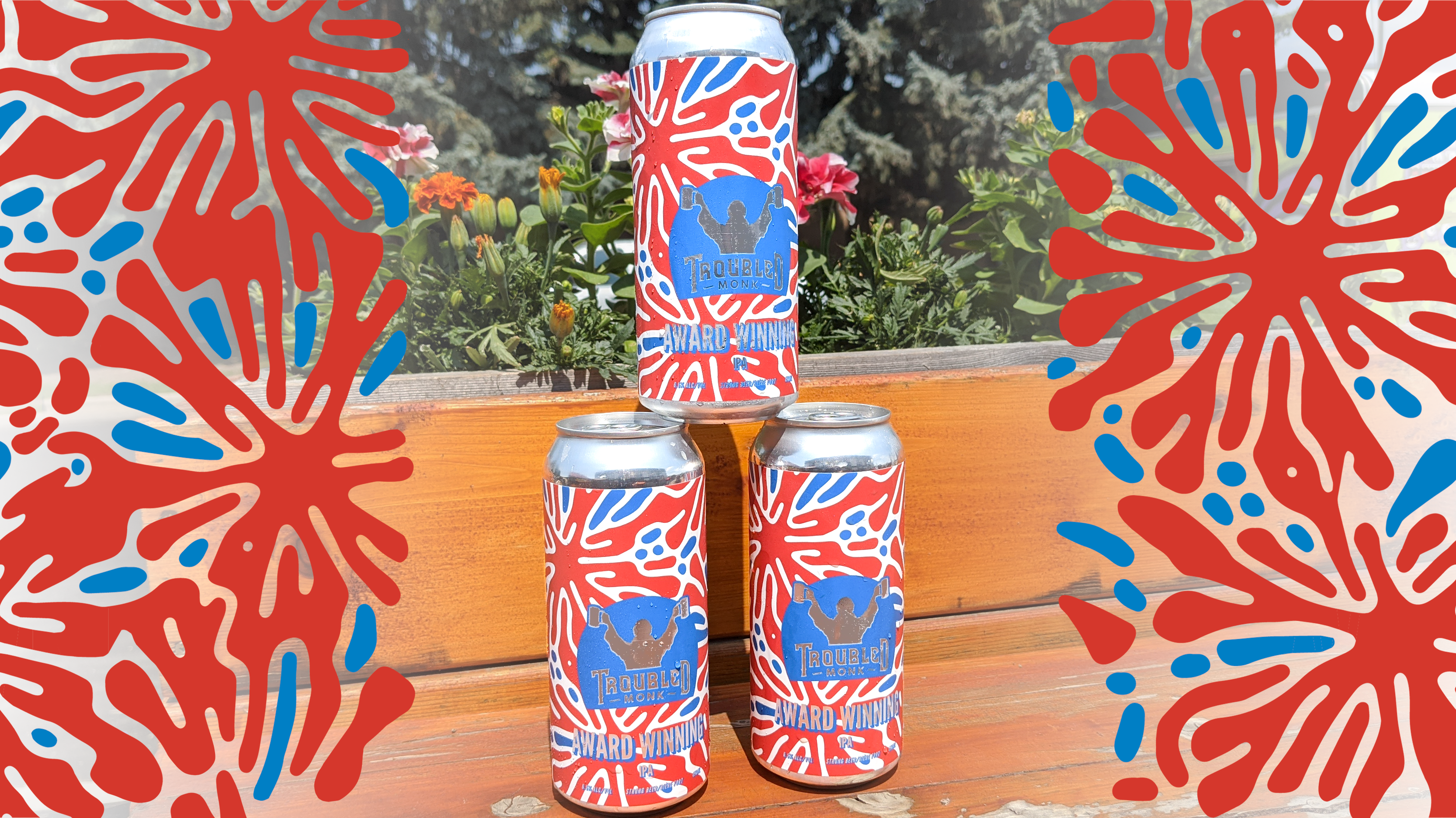 a picture of three cans of troubled monk award winning hazy ipa sitting on the patio with flowers behind. The can is blue and red and blue and red graphics frame the three can stack.
