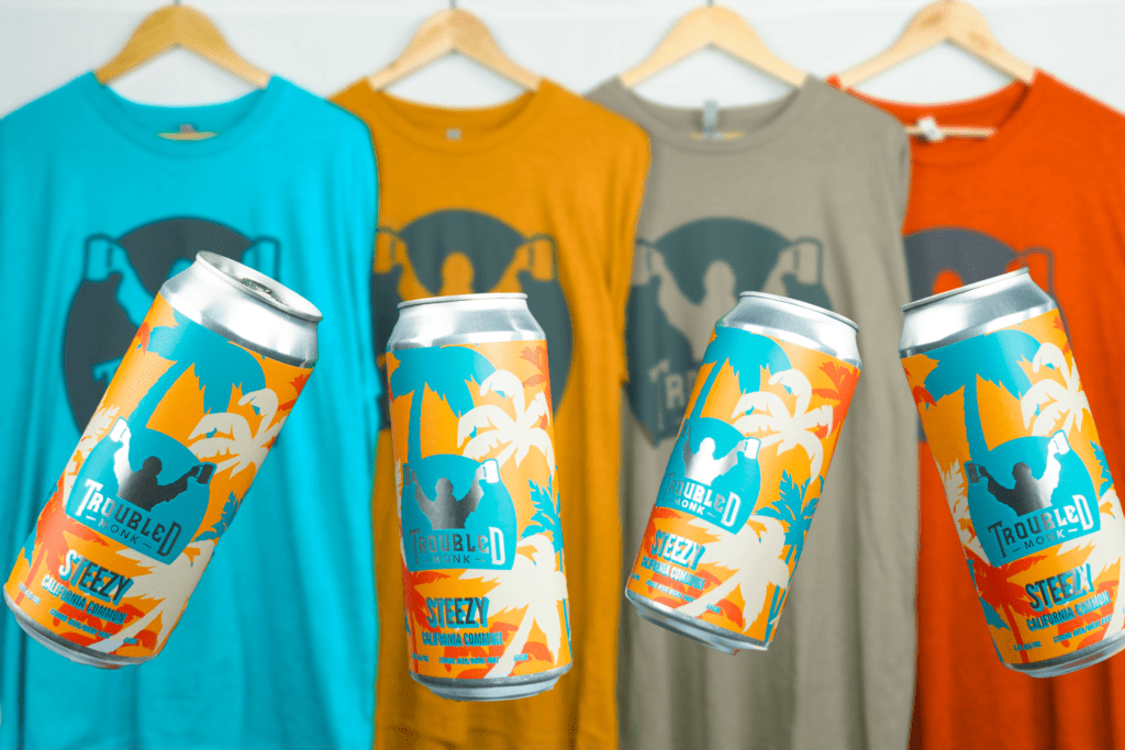 Steezy cans next to Troubled Monk shirts in turquoise, pumpkin orange, brown, and bright orange