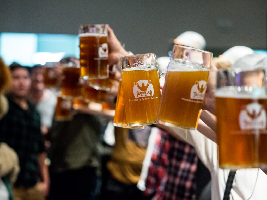 Picture from Oktoberfest 2019 with steins of troubled monk's oktoberfest beer being raised in the air