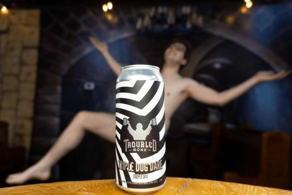 a picture of troubled monk's triple ipa with konner in the background blurred out, but seemingly naked, was he triple dog dared?